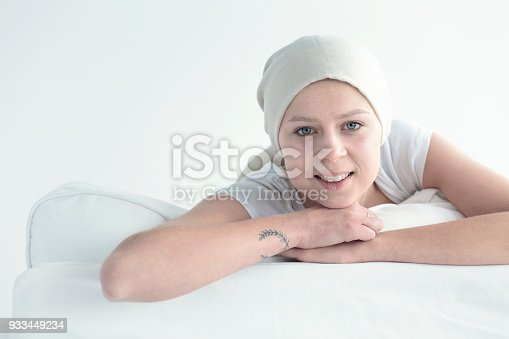 A smiling woman wearing a head scarf and sitting on a couch