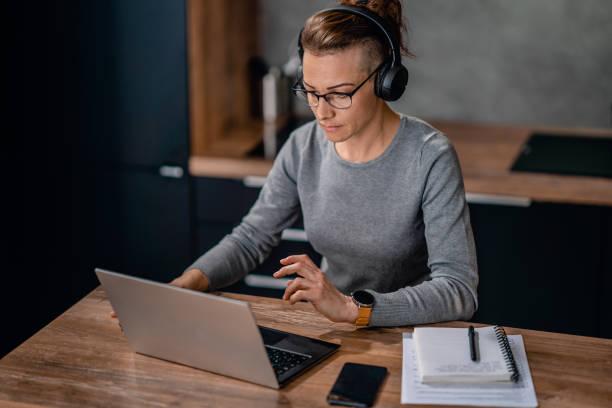 Woman wearing headphones and watching a webinar stock photo