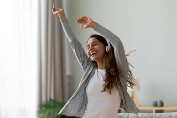 mulher que desgasta auscultadores que dançam na sala de visitas em casa - dançar - fotografias e filmes do acervo