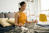 istock Woman wearing headphones sitting at home in the bed in lotus position, while meditating 1318457433