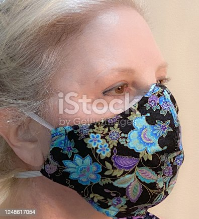 Senior caucasian woman wears a protective mask she made to help protect from catching the coronavirus.