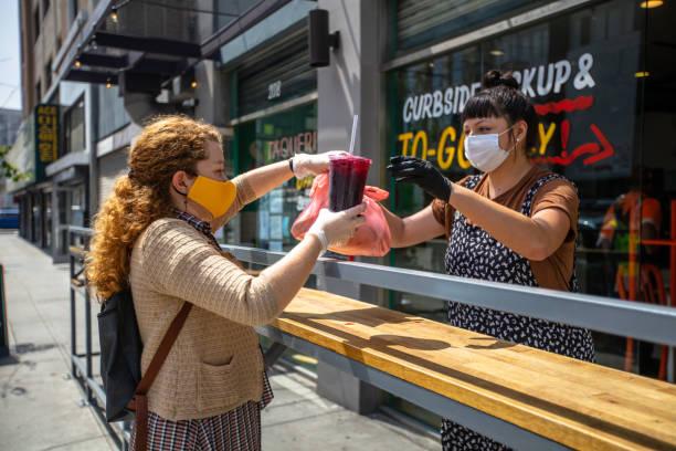 mujer que usa máscara casera recoge comida en el restaurante durante el bloqueo de covid-19 - restaurante fotografías e imágenes de stock