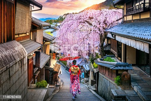 Woman wearing japanese traditional kimono walking at Historic Higashiyama district in spring, Kyoto in Japan.
