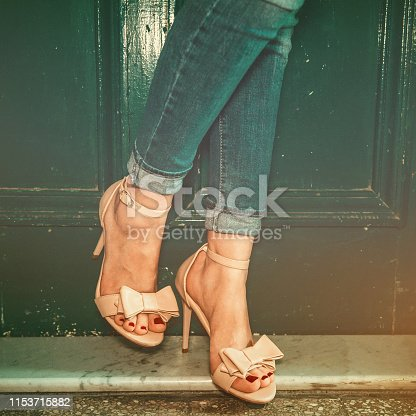 High heels sandals on beautiful thin female legs, shot at the stairs inside an old building