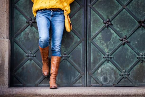 frau trägt jeans, gestrickter pullover und lederstiefel lehnt sich an ein altes tor. - handtasche jeans stock-fotos und bilder