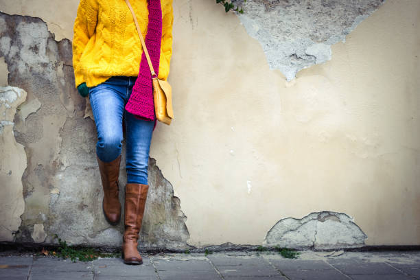 Woman wearing jeans, yellow knitted sweater, woolen scarf, handbag and leather boot. Fashion model standing at wall in city. boot stock pictures, royalty-free photos & images