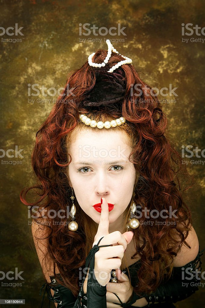 Woman Wearing Jewellery Beads in Hair Holding Finger to Lips royalty-free stock photo