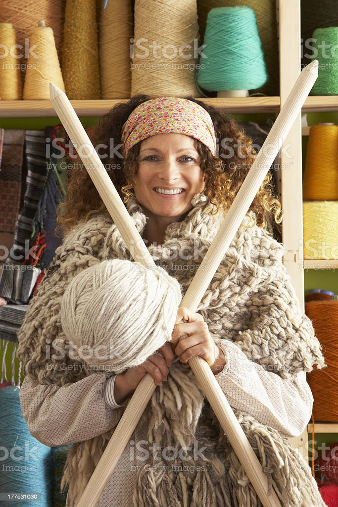 Woman Wearing Knitted Scarf Standing In Front Of Yarn Display royalty-free stock photo