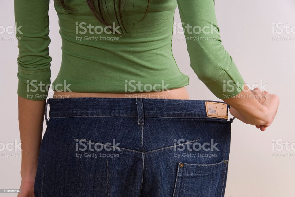 Woman wearing large jeans stock photo