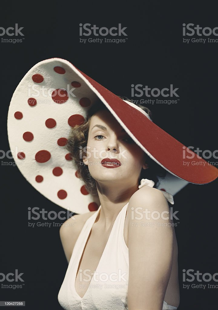 Woman wearing large spotted hat, portrait stock photo
