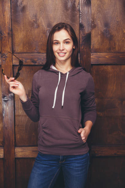 frau trägt magenta sweatshirt vor holzwand - fleecepullover stock-fotos und bilder