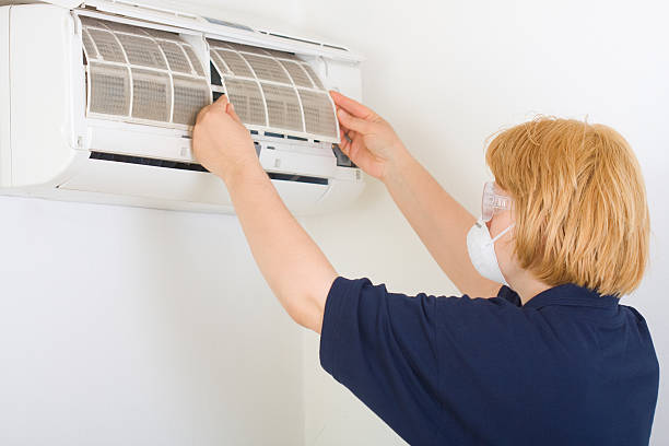 Woman wearing mask and goggles cleans out an air conditioner stock photo