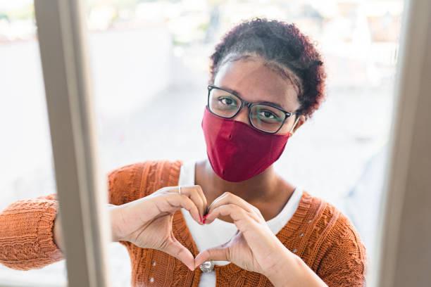 vrouw die masker draagt en hartteken door venster maakt - raam bezoek stockfoto's en -beelden