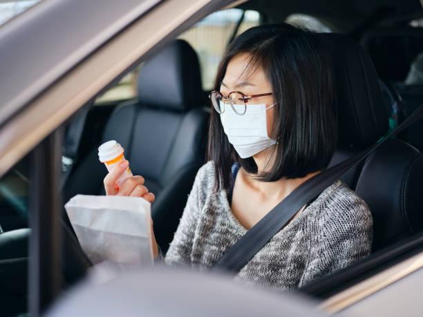 Woman Wearing Mask at Drive-Through Pharmacy stock photo