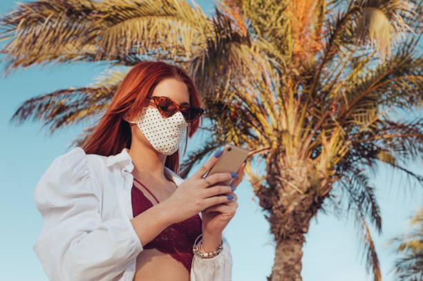 Woman wearing mask using phone stock photo