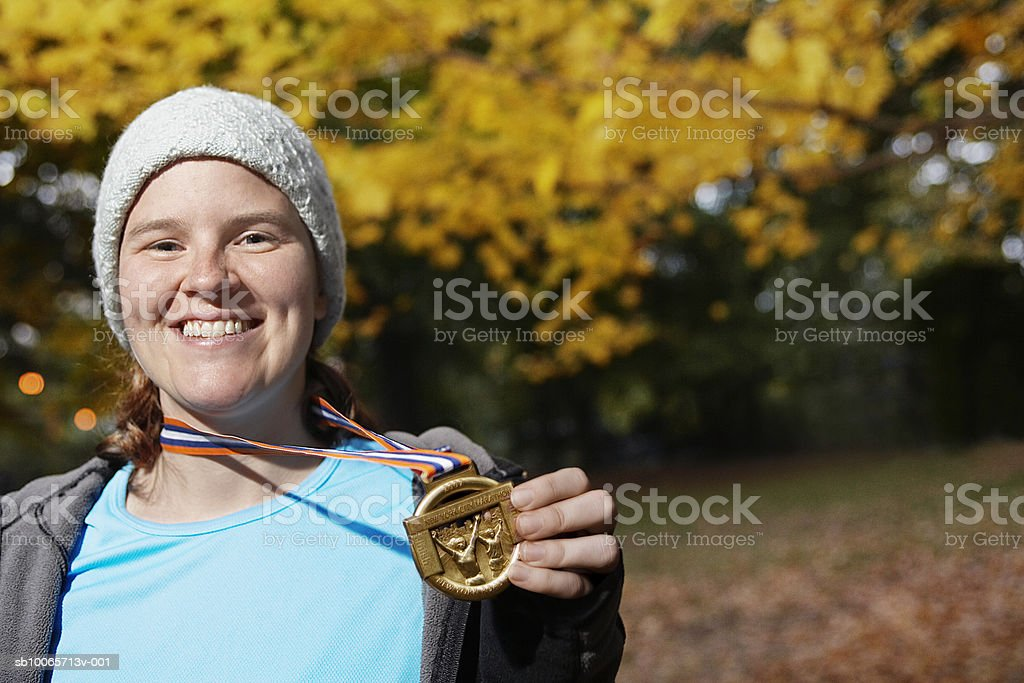 Woman wearing medal, smiling, portrait royalty free stockfoto