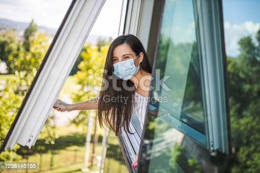 Woman wearing medical face mask, staying home for safety and looking through window during coronavirus pandemic