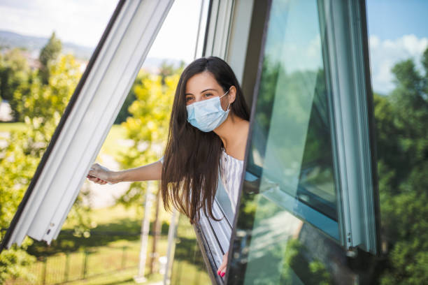 woman wearing medical face mask, staying home for safety and looking through window during coronavirus pandemic - open window imagens e fotografias de stock