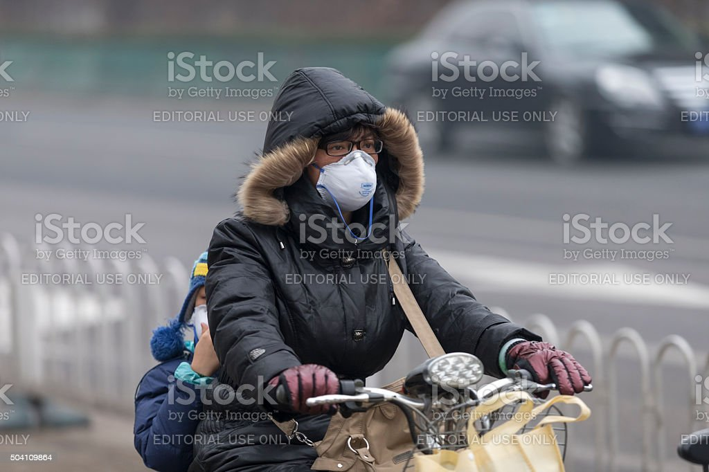 Woman wearing mouth mask with filter against air pollution, Beijing stock photo