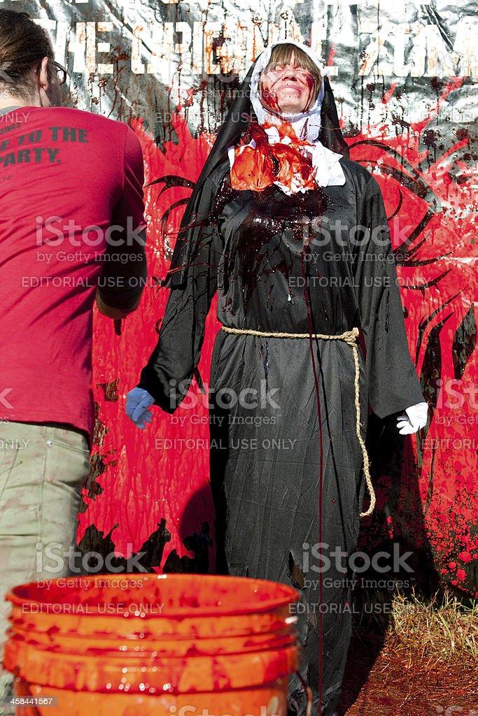 Woman Wearing Nun Costume Gets Fake Blood Splattered On Habit stock photo