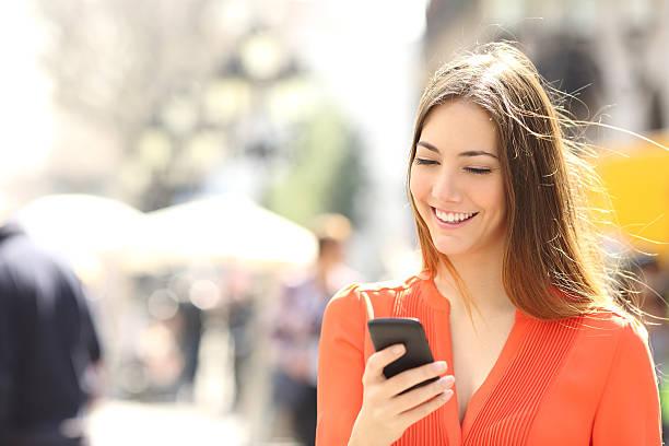 frau mit orange shirt sms auf smart phone - outdoor handy stock-fotos und bilder