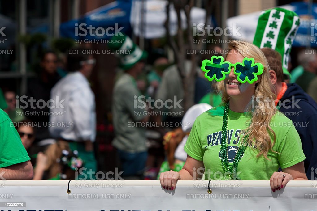 Woman Wearing Oversized Shamrock Sunglasses Carries Banner In Parade stock photo