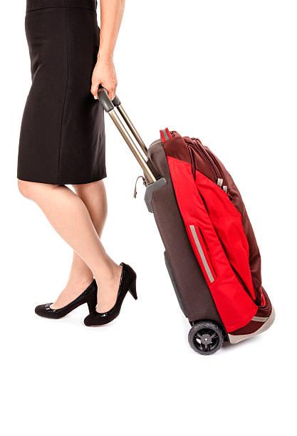 frau mit bleistiftrock ziehen eine kleine reisen gepäck - rote bleistiftröcke stock-fotos und bilder