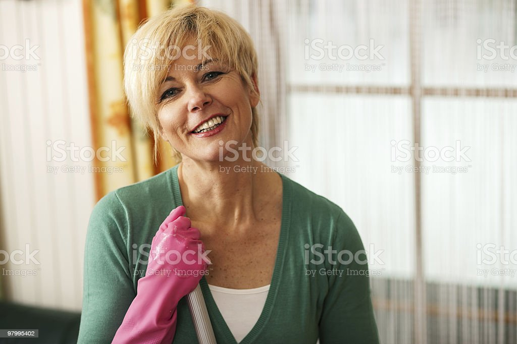 Woman wearing pink cleaning gloves to mop the floor royalty free stockfoto