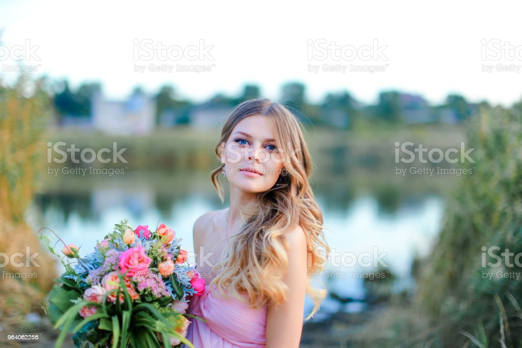 Woman wearing pink dress with bouquet of flowers standing near lake - Royalty-free Adult Stock Photo