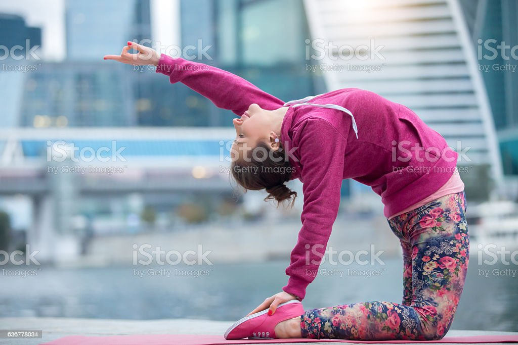 Woman wearing pink sportswear in Camel pose against city backgro stock photo