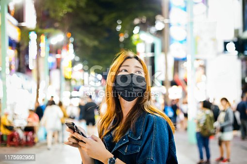 Woman wearing pollution mask while using mobile phone. Young female is looking away while standing on street. She is in city at night.