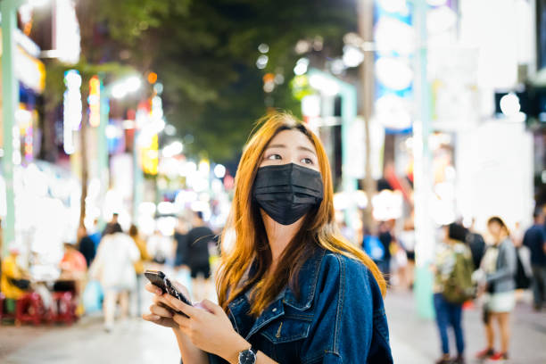 Woman wearing pollution mask while using phone stock photo