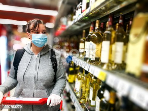 Selective focus color image depicting a caucasian woman in her 30s wearing a protective surgical face mask and plastic surgical gloves  during the coronavirus (Covid-19) pandemic, in a bid to stop the spread of the virus. The woman is pushing her shopping cart inside a supermarket while shopping for wine and alcohol in the alcoholic drinks section of the store. Room for copy space.