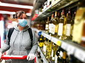 istock Woman wearing protective face mask and gloves shopping for alcohol in supermarket 1220753279