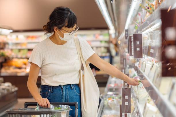 スーパーマーケットでの病気予防と買い物のための保護フェイスマスクを着用した女性 - スーパーマーケット 日本 ストックフォトと画像