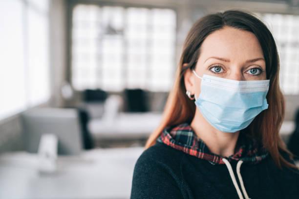 Frau trägt schützende Gesichtsmaske im Büro für Sicherheit und Schutz während COVID-19 – Foto