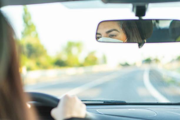 vrouw die beschermend gezichtsmasker draagt terwijl het drijven van auto. reflectie in spiegel. - mirror mask stockfoto's en -beelden