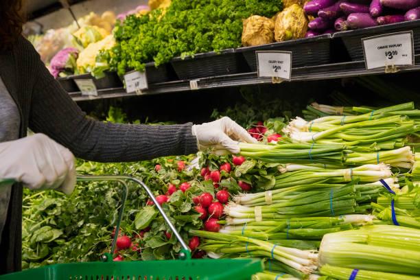 Frau mit Schutzhandschuhen beim Einkaufen im Supermarkt. – Foto