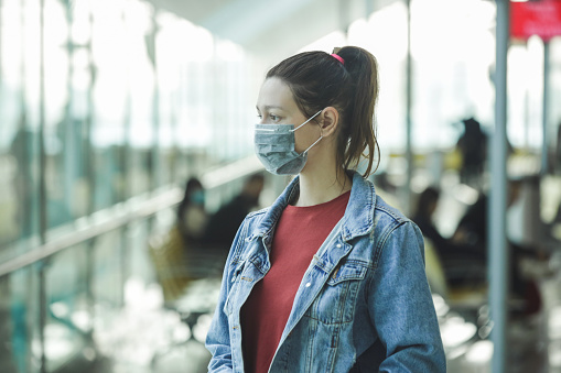 istock Woman wearing protective mask in airport, Coronavirus contagion fears concept 1208604215