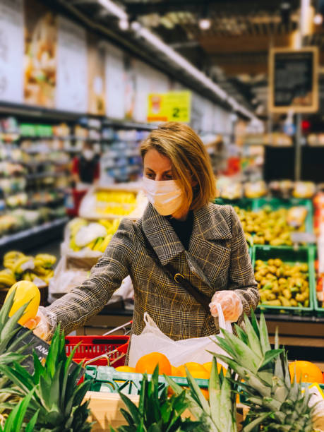 Woman wearing protective mask shops for groceries stock photo