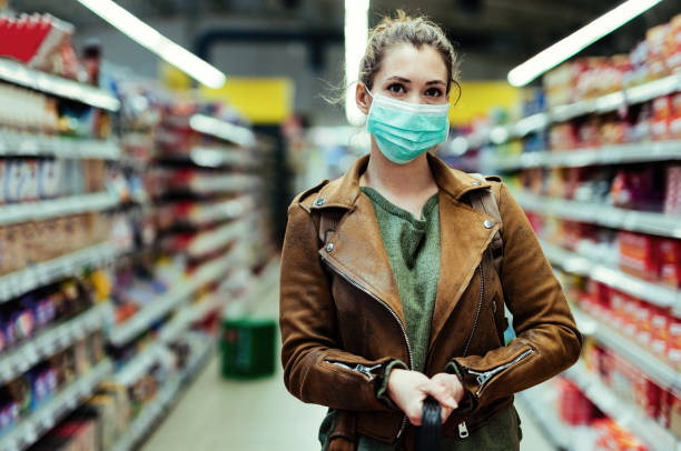 Woman wearing protective mask while buying supplies in time of virus epidemic. stock photo