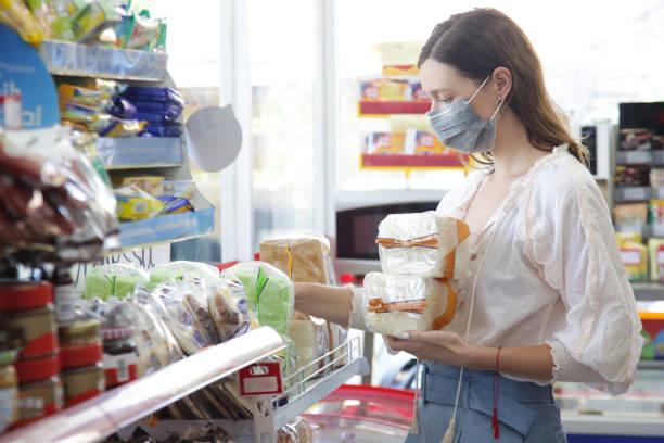 Frau trägt Schutzmaske beim Einkaufen im Supermarkt, Coronavirus Ansteckung fürchtet Konzept – Foto