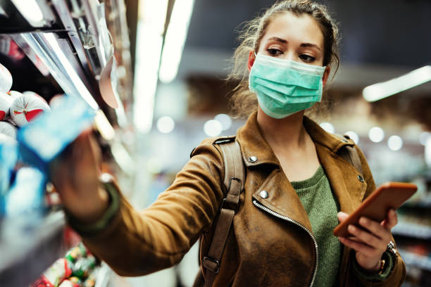 woman wearing protective mask while using cell phone and buying food in grocery store during virus epidemic. - máscaras imagens e fotografias de stock