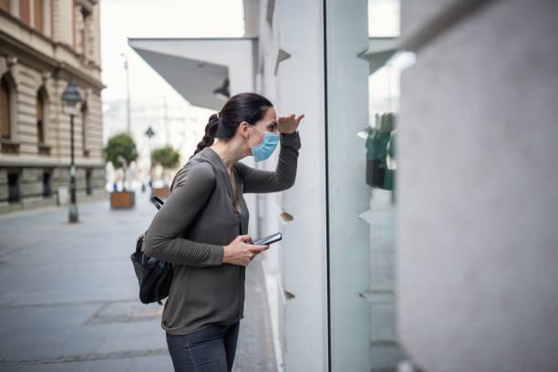 Frau trägt Schutzmaske, Schaufenstereinkauf – Foto