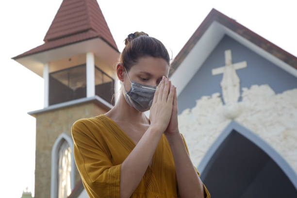 Frau trägt schützende medizinische Maske vor der Kirche. Religiöses Hoffnungskonzept in schwierigen Zeiten. Corona-Virus-Ausbruch und Luftverschmutzungskonzept. – Foto