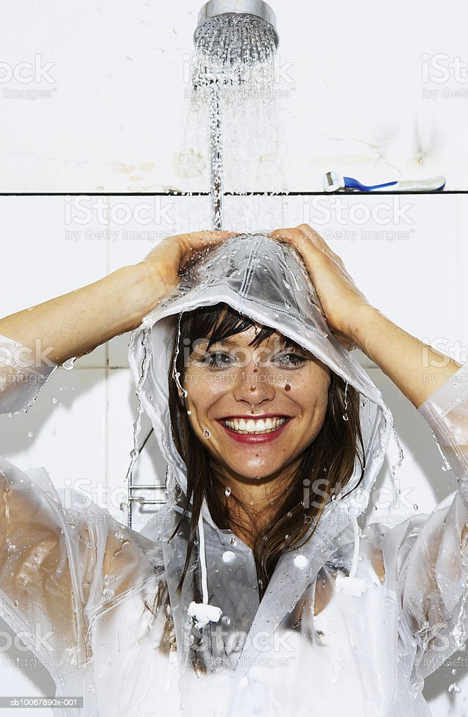 Woman wearing raincoat having shower in bathroom, smiling, portrait royalty-free stock photo