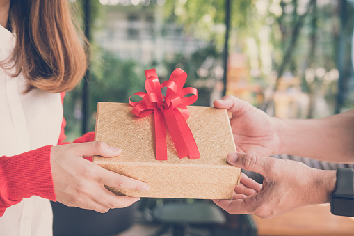 young woman wearing red cardigan give gift box to a man. hand get present box. christmas, new year holiday. valentine, birthday, anniversary celebration.