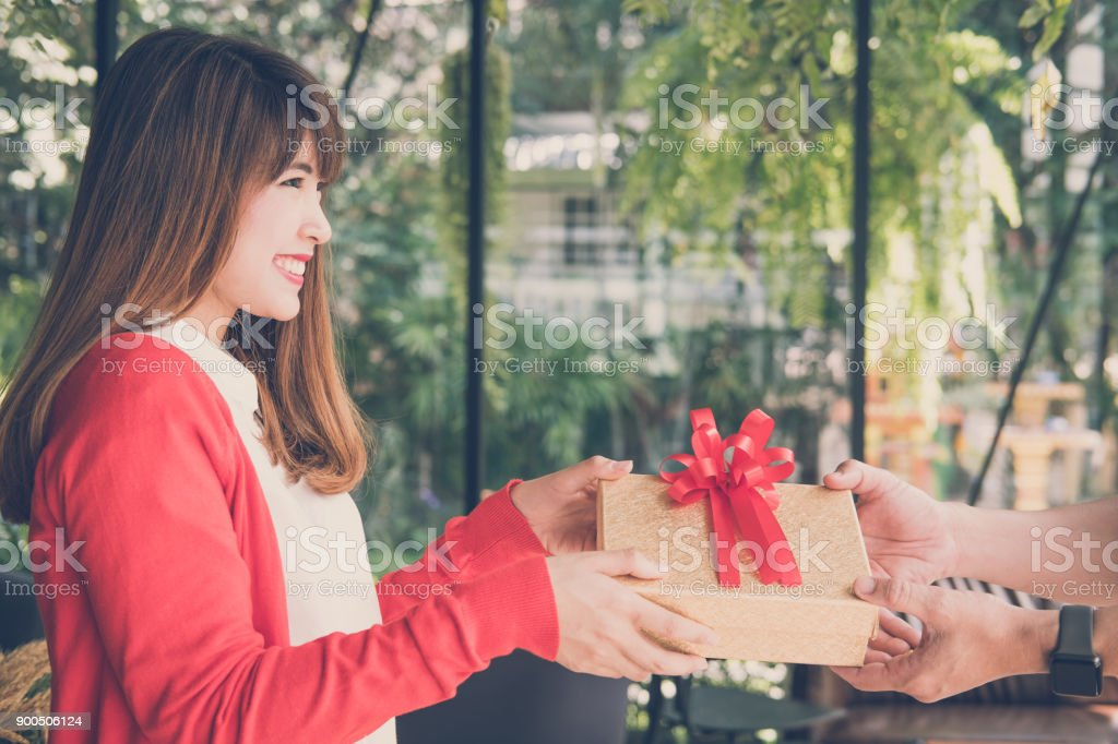 woman wearing red cardigan give gift box to a man. hand get present box. christmas, new year holiday. valentine, birthday, anniversary celebration. stock photo