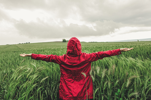Woman wearing red raincoat out in the rain