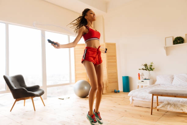 Woman wearing red shorts and top skipping the rope at home stock photo